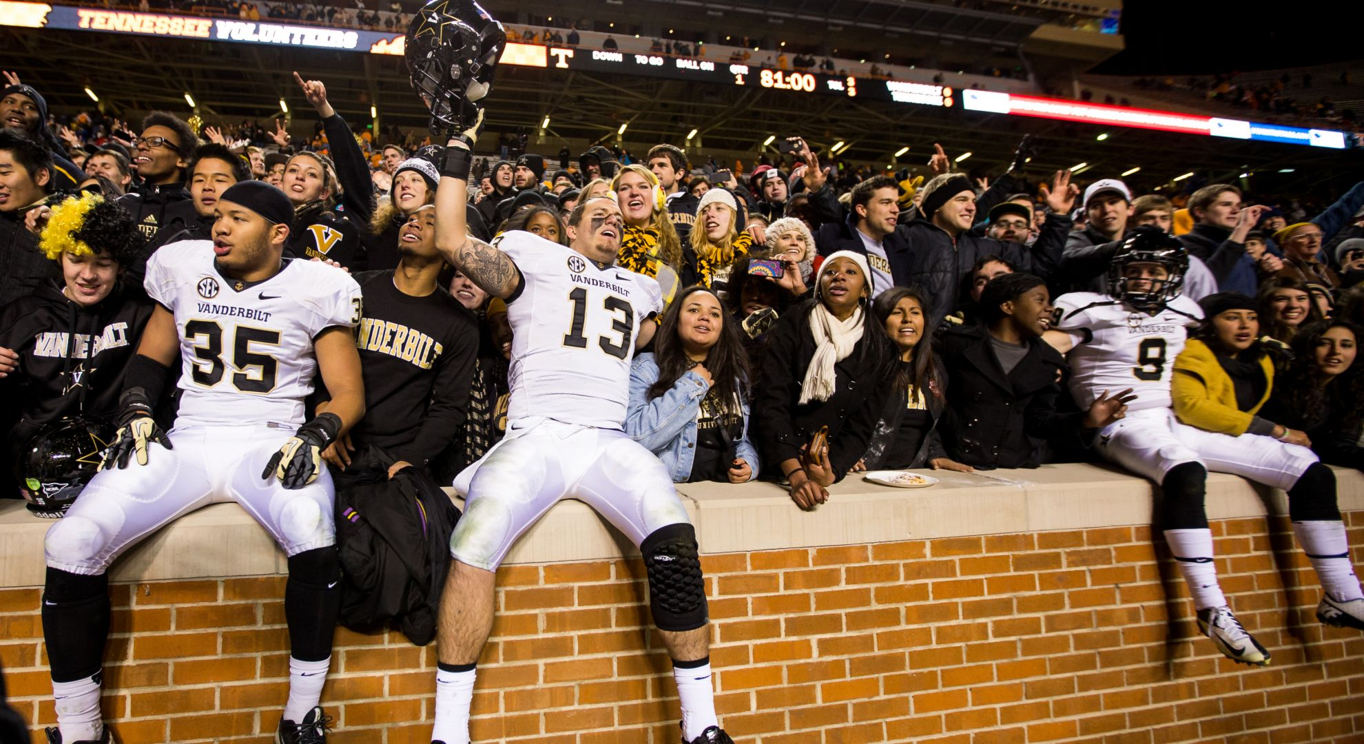 Commodore players celebrate with fans after defeating Tennessee.